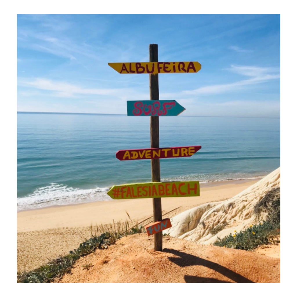 A colourful wooden sign on a beach in Portugal. The sign gives the options to go towards Albufeira, surf, adventure, #falesiabeach or fun