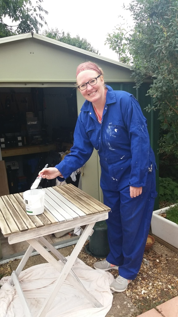 Me in blue overalls smiling at the camera as a paint a wooden table with a white wash in front of a metal shed