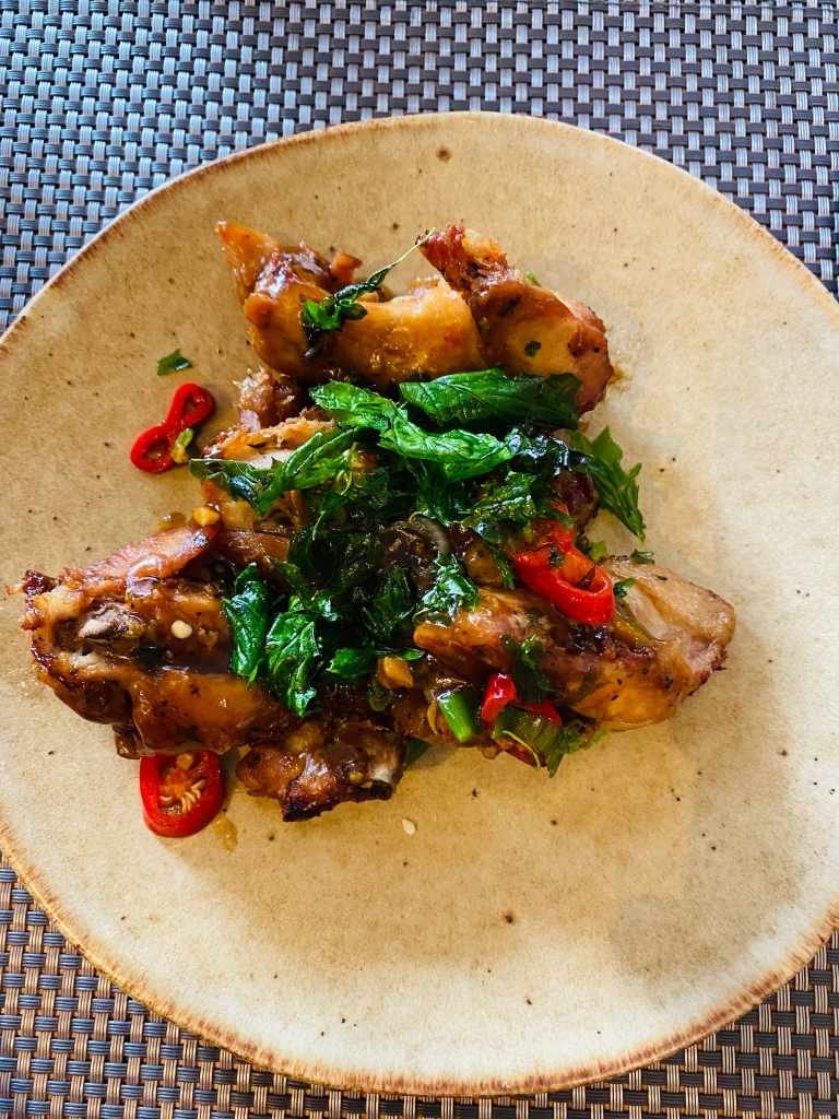 A close up of a plate of chicken wings with green leaves and chillis