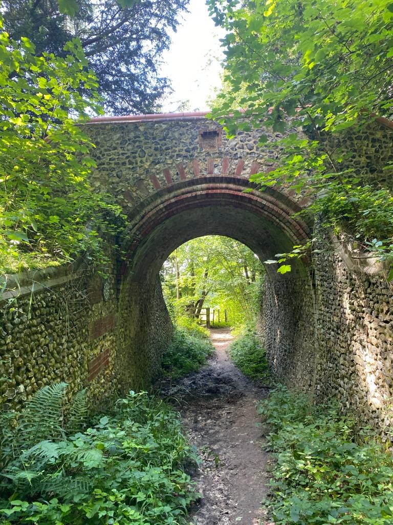 An old horseshoe shaped brick bridge in the woodland