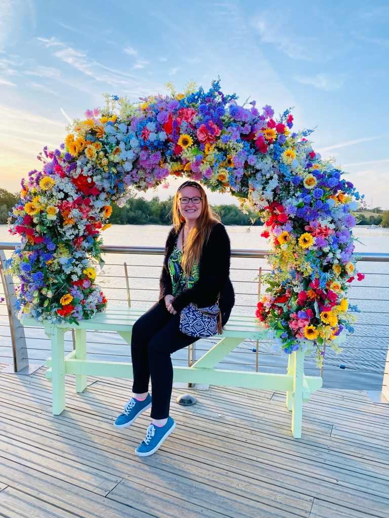 A photo of me smiling sitting underneath the colourful arched floral display with a lake behind me