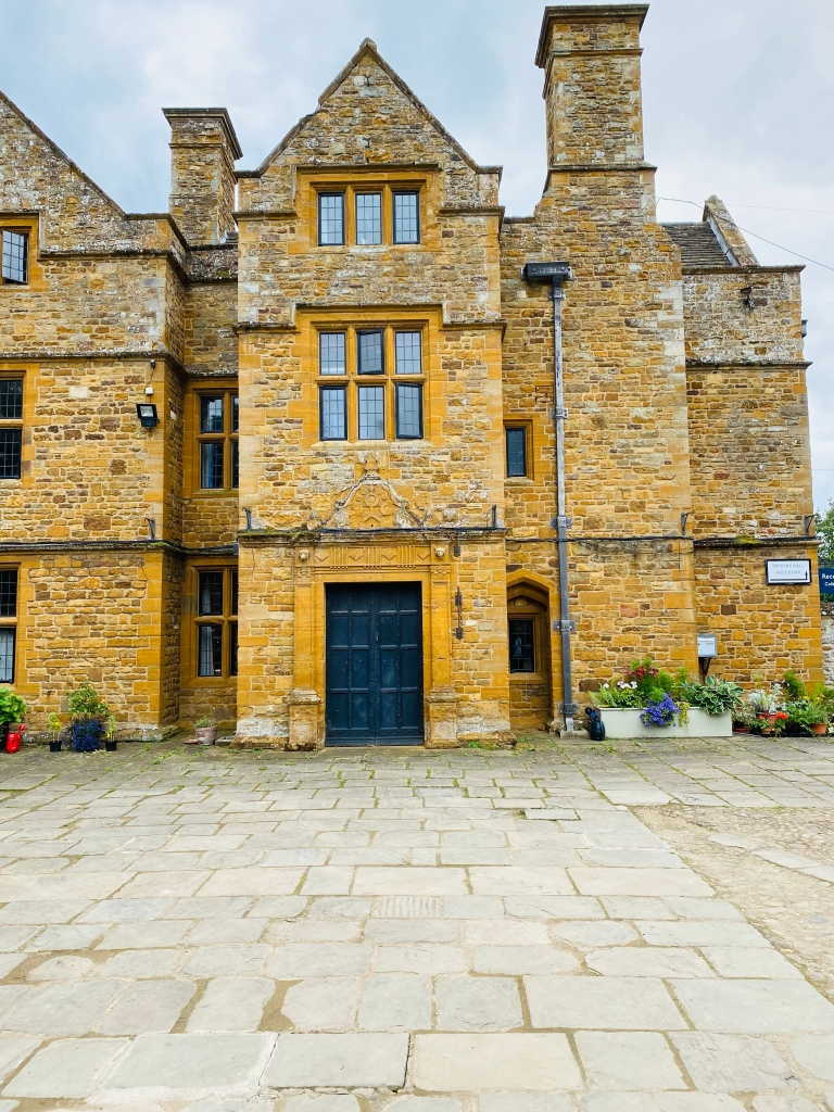 The outside of Thornby Hall with a small floral display in containers either side of the building