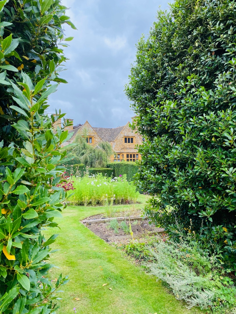 A view of Thorny Hall from the flower gardens. There are tall bushes either side of the walk way which opens up into flower beds