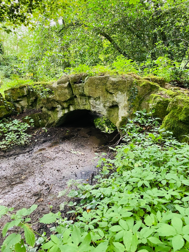 An old low stone bridge surrounded by woodland. The river beneath it is dry