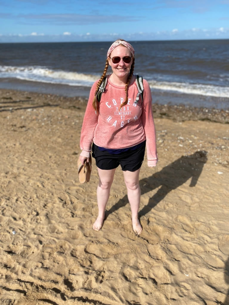 Me standing on the sand with the sea in the background. I'm wearing black shorts and a pink sweatshirt. My flip flops are in my hand and I have pigtails