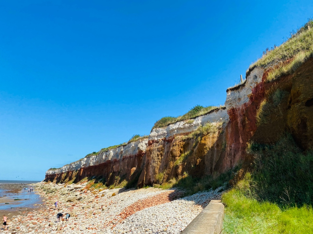 Tall cliffs to the right of the photo with multiple different coloured layers. There are rocks below and a bright blue sky