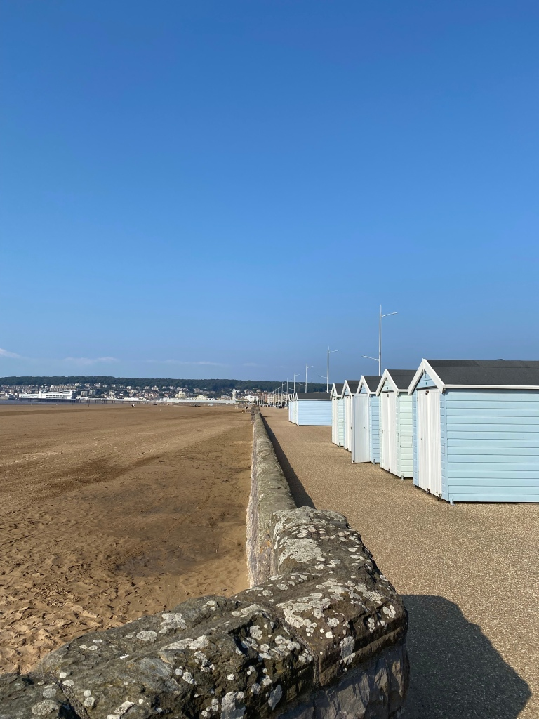Blue and white beach huts on the right hand side of the photo. Adjacent to the beach huts it a wall with the beach to the left hand side . The sky is bright blue. You can see Weston super Mare in the distance