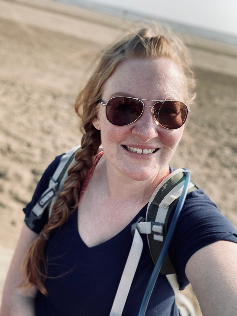 A selfie of me, with my hair in a plait over my right shoulder. I have sun glasses on, a navy blue t-shirt and a rucksack. You can see the beach behind me