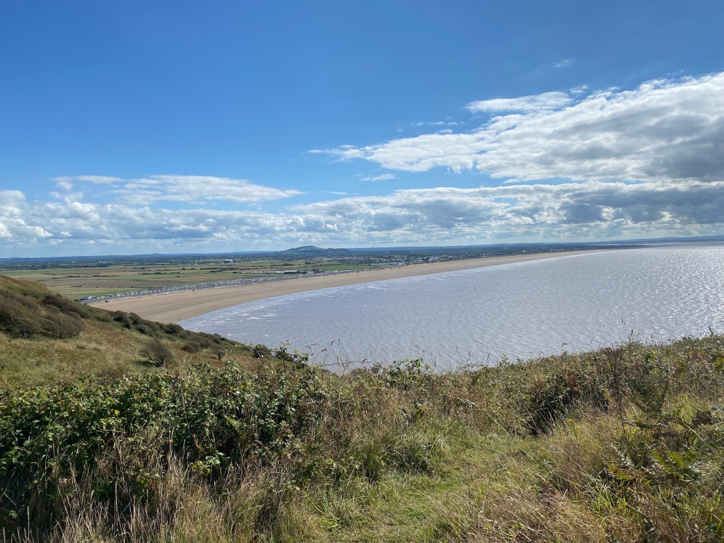A view from the top of Brean Down looking down on the sea and the beach