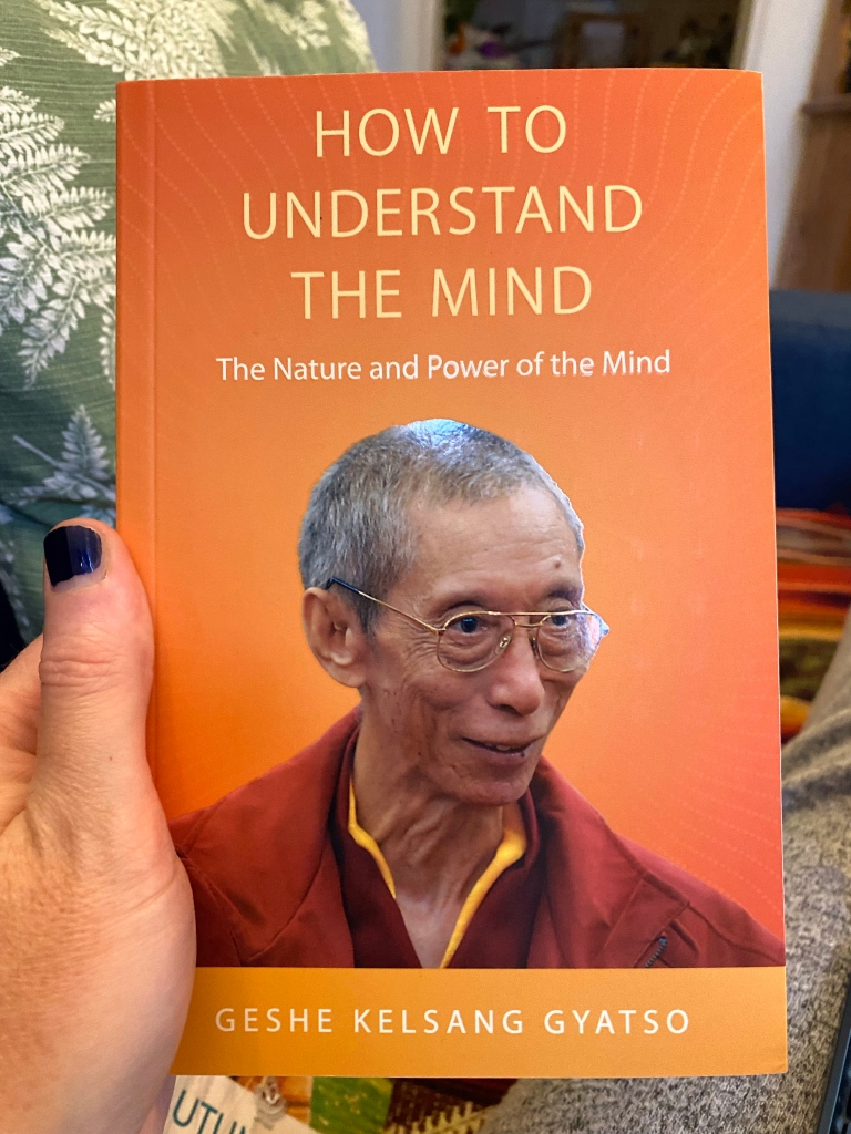 The book cover for How to Understand The Mind by Geshe Kelsang Gyatso. The cover is bright orange and has a picture of Geshe on the front. He looks to be a budhist monk and is wearing glasses